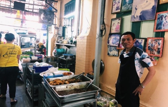 Shop owner standing in front of food store