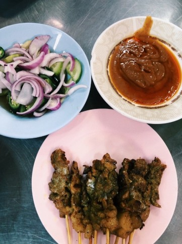 A plate of beef satay sticks alongside onions, chillis and sweet sauce
